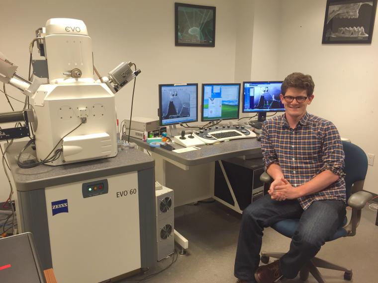 Henry Towbin '13 posed next to microscope
