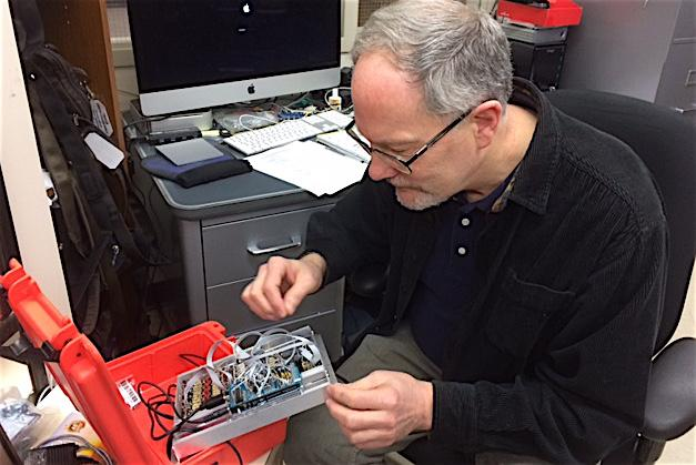 John Talbert inspects wires in an electronic component