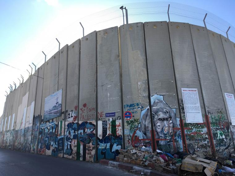 A huge concrete wall is covered in graffiti and topped with barbed wire.