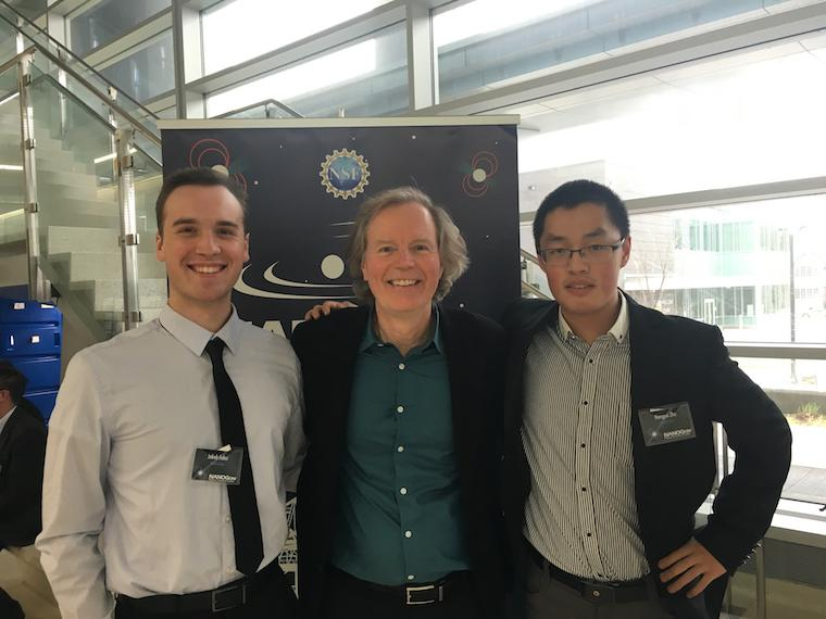 Two male students pose on either side of their male professor