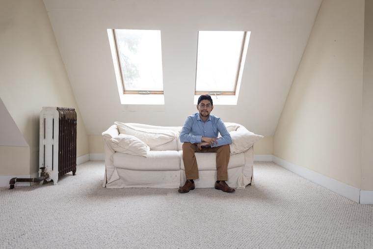 Photo of Jesus Martinez seated on a white couch in a room with skylights behind him