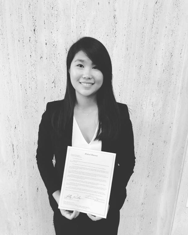 black and white image of Asian woman holding a piece of paper.