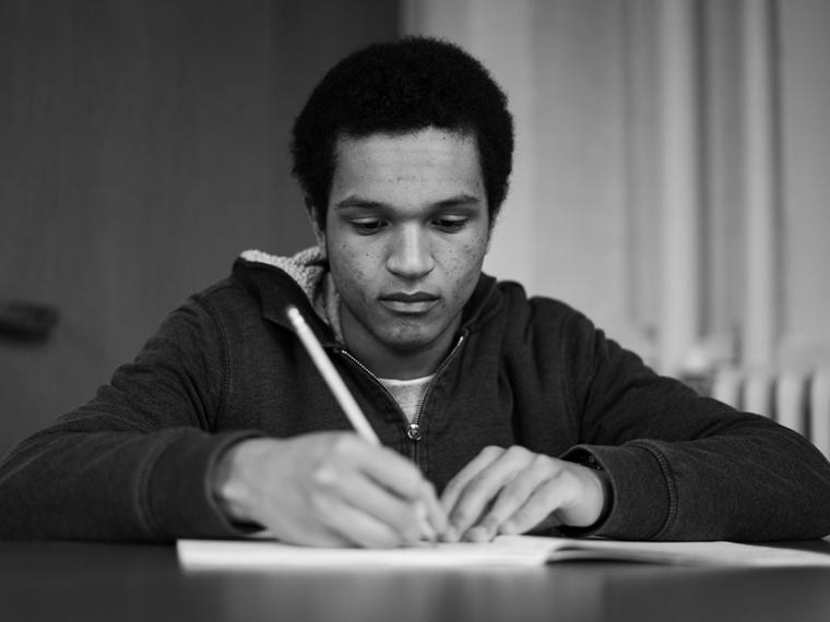 a young black man writing with a pencil in a book.