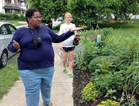 Two women tour a garden along a city sidewalk