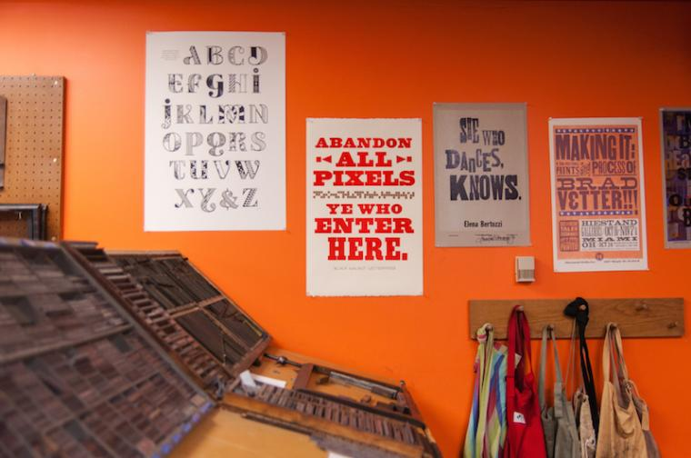 On a wall behind the letterpress equipment, one of several posters reads, 'Abandon all pixels ye who enter here.'