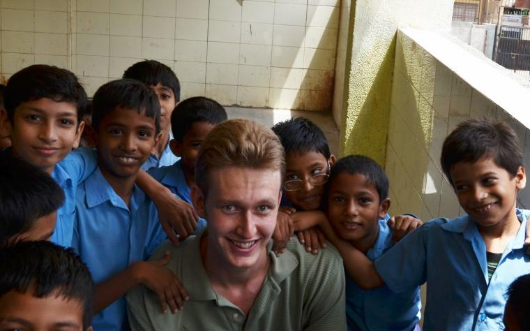team member and rising junior Thomas Kreek with young students in New Delhi