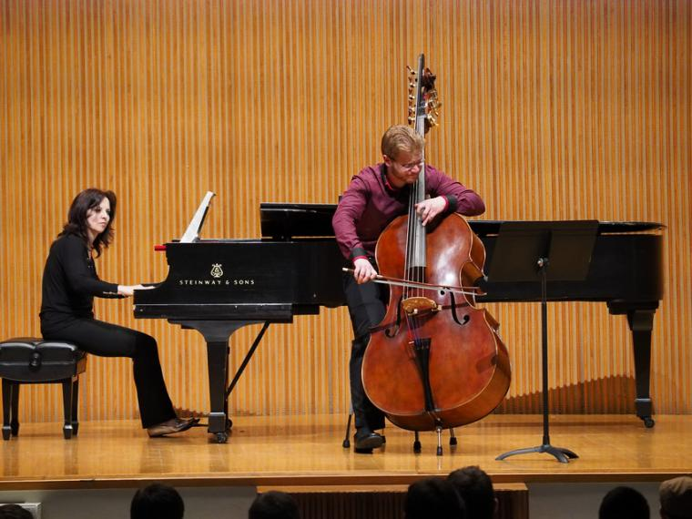 A bassist plays with a bow and is accompanied by a pianist.