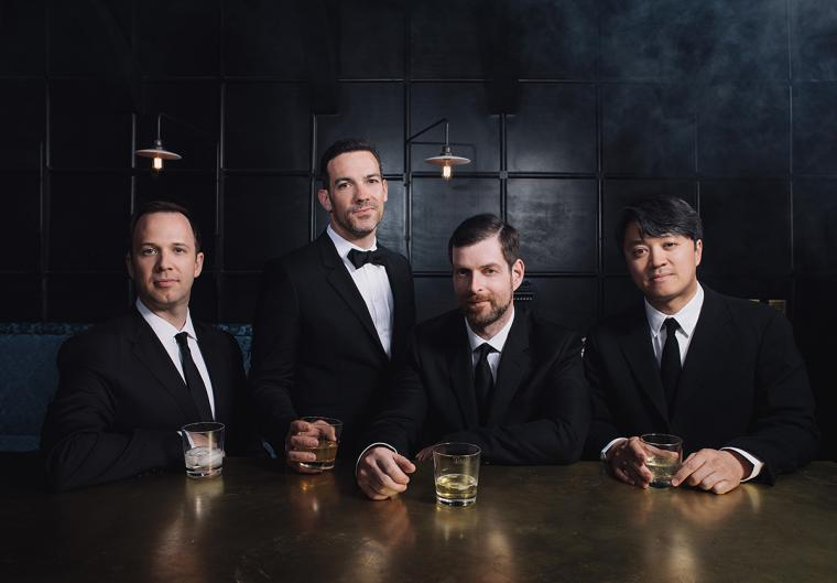 Four men in black suits seated at a bar