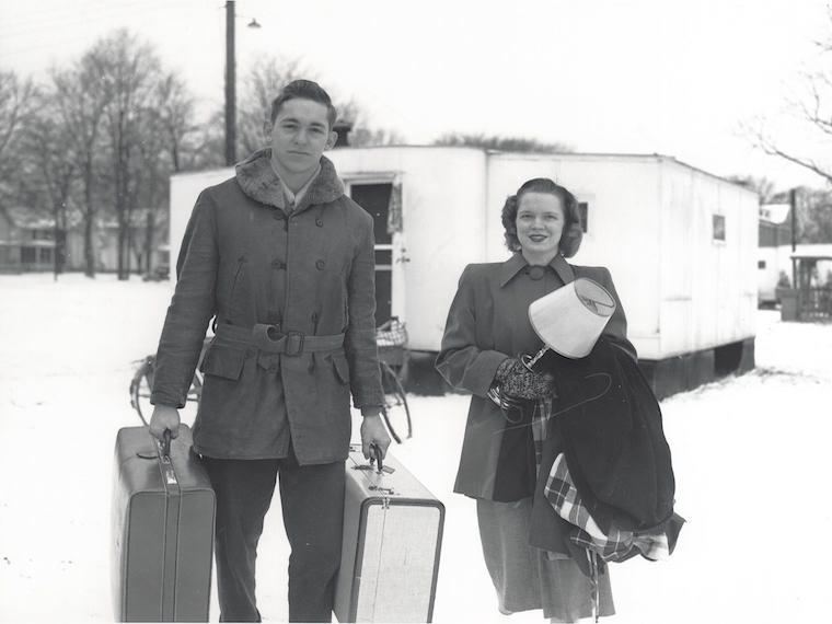 military veteran with his wife outside of a trailer during the winter.