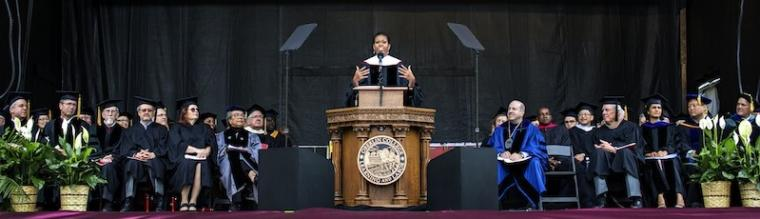 Michelle Obama speaks at a podium bearing the Oberlin College seal. Dignitaries in academic robes are seated on both sides.