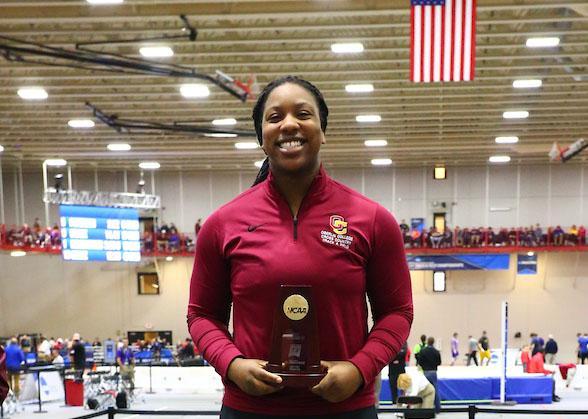 Monique Newton holding an NCAA trophy.