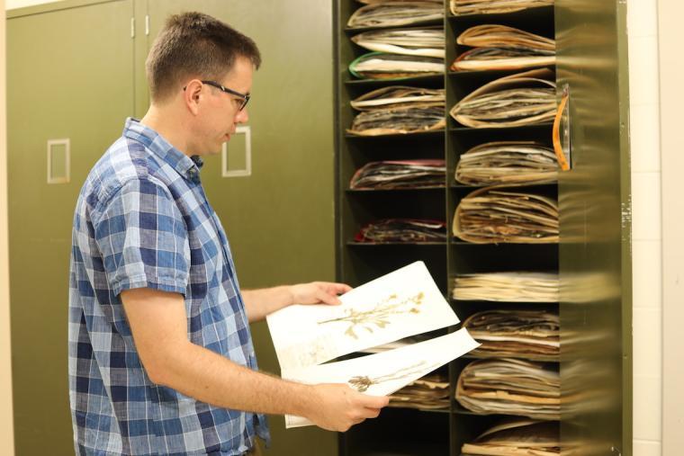 Professor Michael Moore holding plant specimens