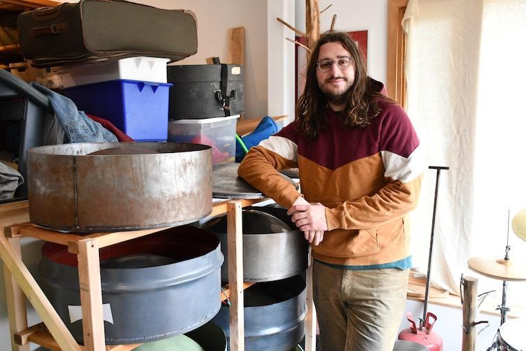 Noah Sanderson leaning against racks filled with steel pan. Photo.