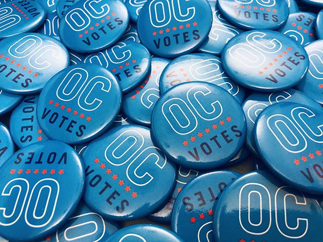 A pile of buttons printed with the OC Votes logo.