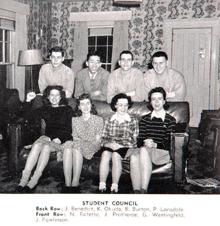 Eight students in a 1940s living room.