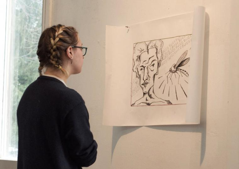 A student examines a print tacked to the wall.