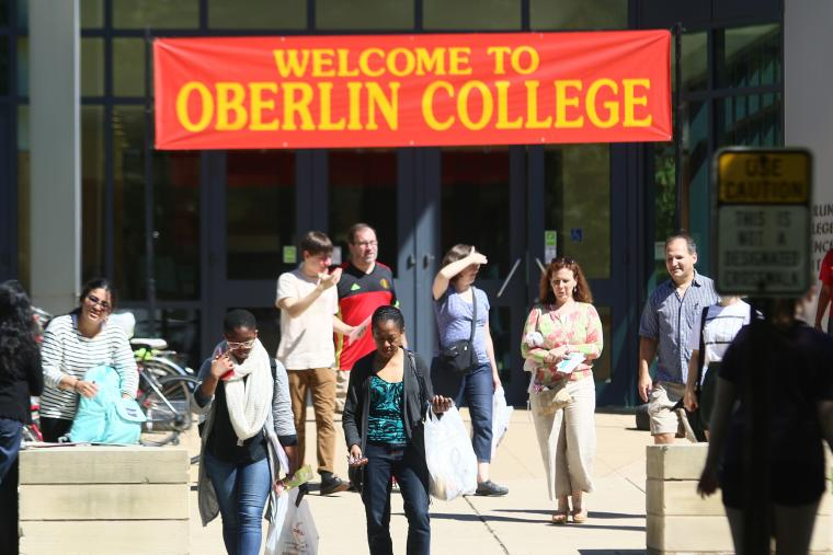 At a building entrance, people walk under a banner reading Welcome to Oberlin College.
