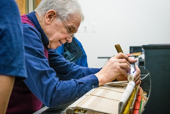 person providing maintenance to a piano