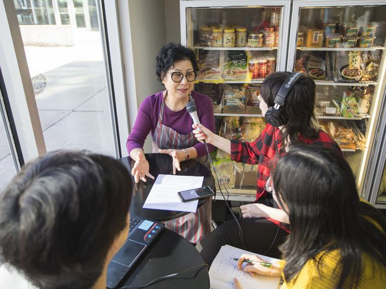 Students interview Kim's Grocery & Carryout owner, Ms. Kim, for their podcast assignment.