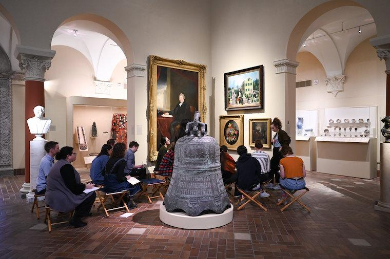 Students look at paintings in the museum while seated in chairs in the gallery.