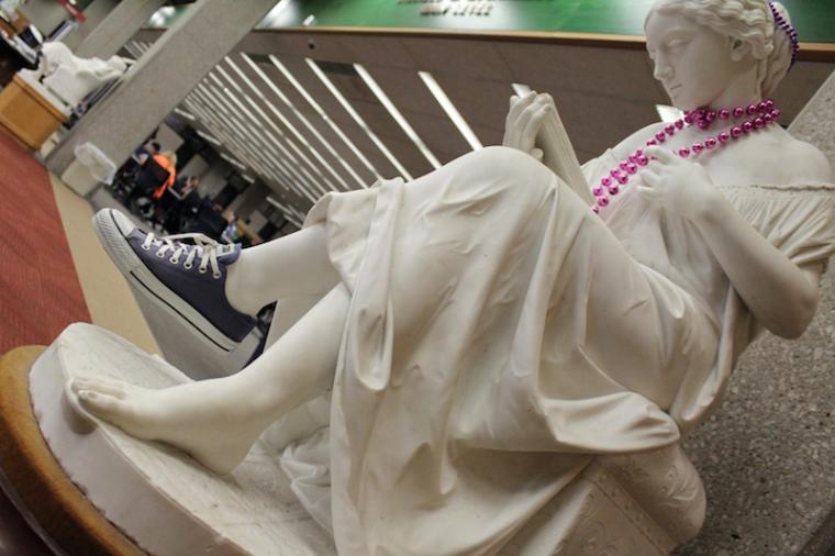 The Reading Girl statue is wearing a Converse sneaker and a bright purple necklace.