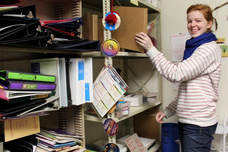 Rosalie Eck places a binder onto a crowded shelf.