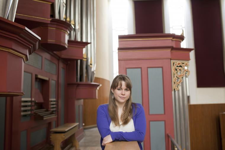 Katelyn Emerson '15 posing next to an organ loft