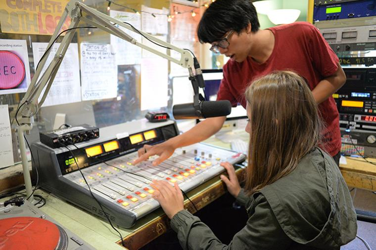 High school students using the soundboard at the WOBC DJ booth