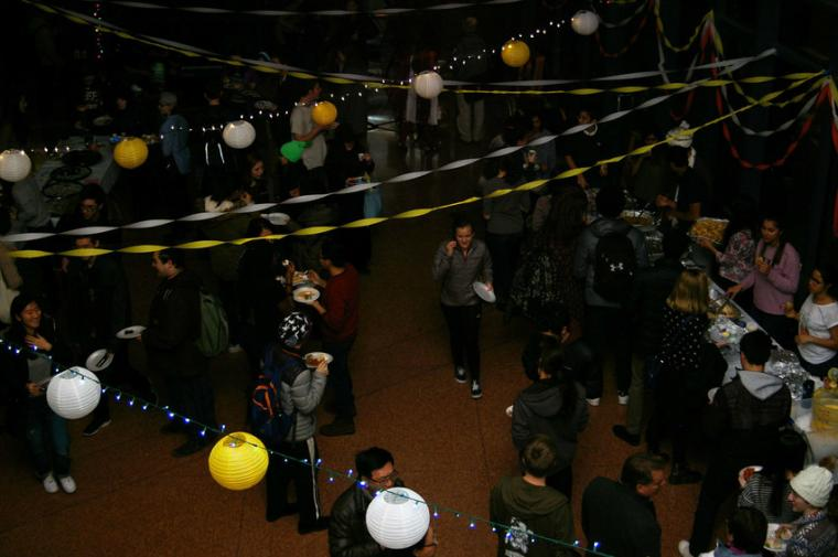 Overhead view of people walking and eating under streamers and Chinese lanterns