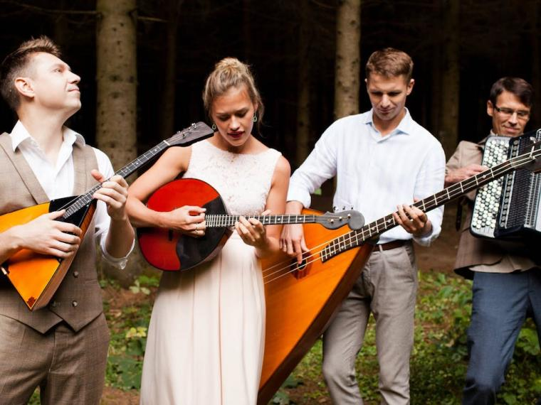 four Russian musicians playing their instruments in a forest
