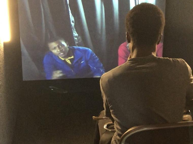 person sitting facing a screen, looking at another person