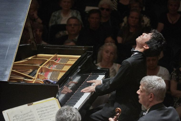 A pianist performs before an audience. He is leaning back with eyes closed and fingers on the keys.