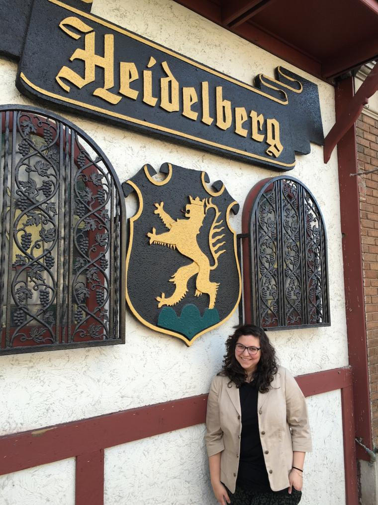 Sarah stands outside an establishment. The sign says 'Heidelberg'.