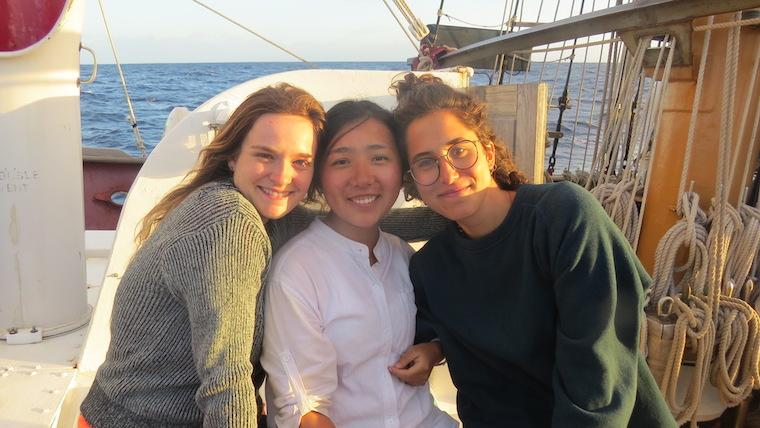 Three people leaning against each other, smiling on a boat. Photo.