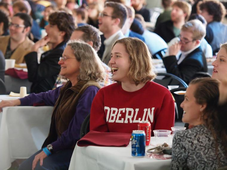 People at a large gathering, seated at tables with tablecloths. Most are smiling.