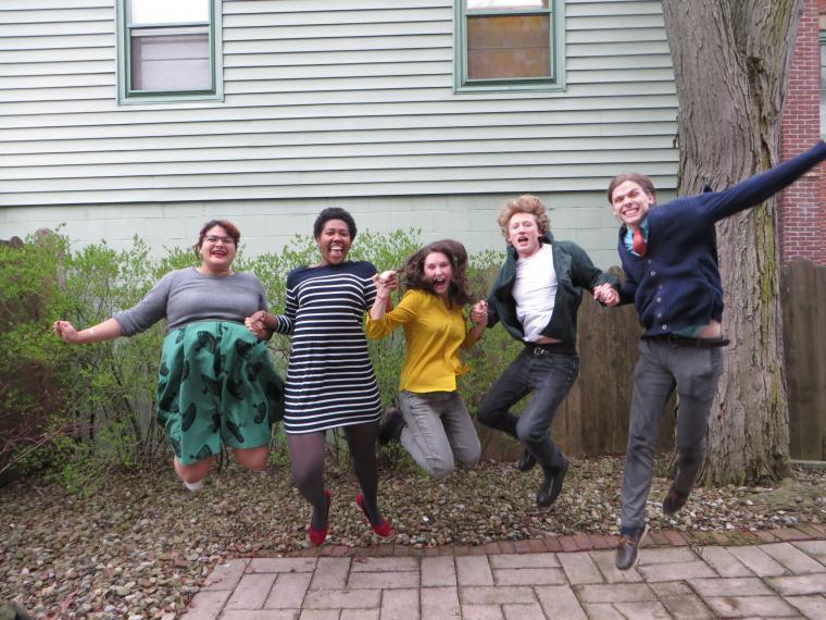 Five Oberlin Shansi fellows holding hands and jumping into the air