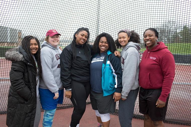 Six women posing by an athletics track