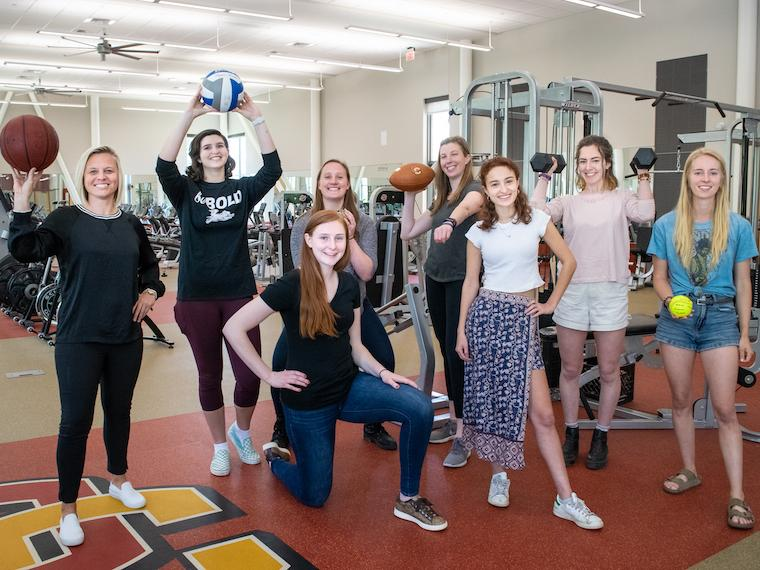 Photo of eight members of the Stronger Together group posing with sports equipment in the gym