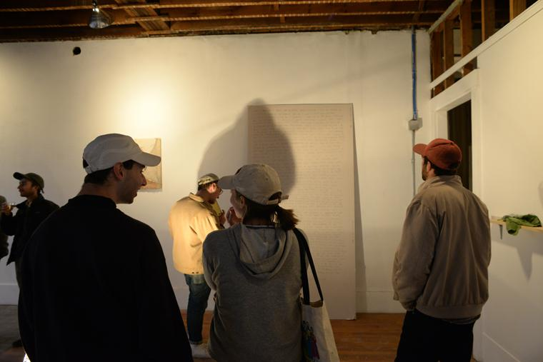 Gallery visitors look at art on the walls of a roughly finished room
