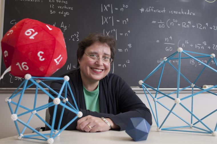 Professor Colley with geometric models on her desk. The blackboard behind her is filled with equations.