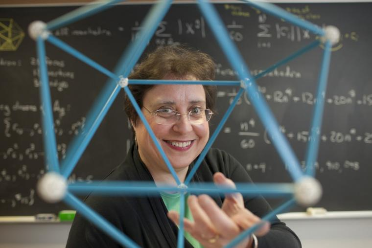 Susan Colley holding a geometric model. In the background, a chalkboard with equations.