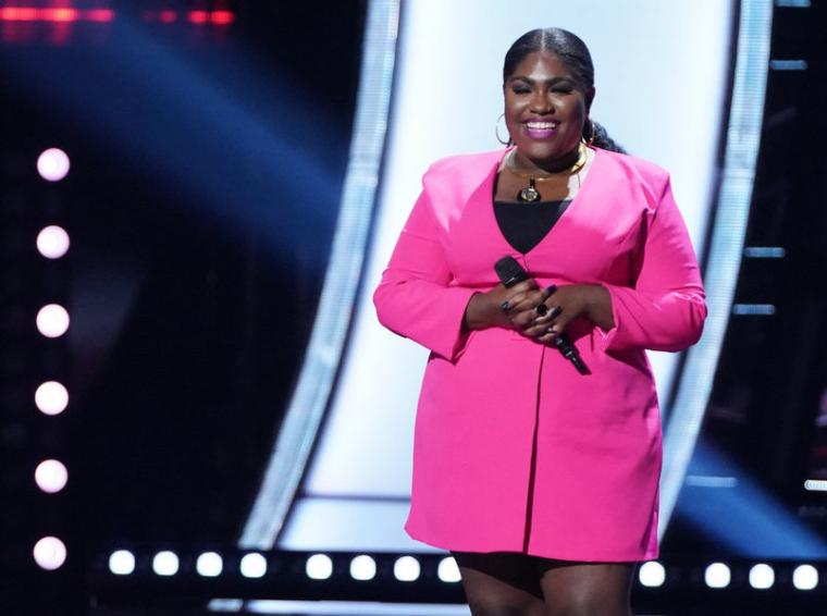 Black woman singer on stage dressed in pink outfit.