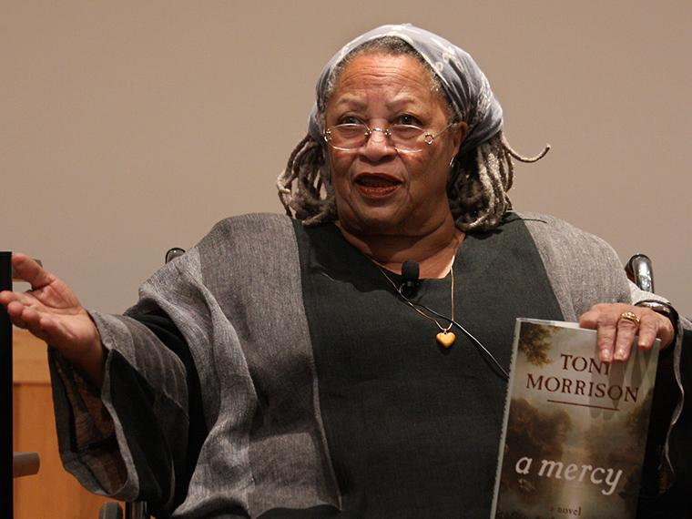 Toni Morrison wearing glasses and holding a book.