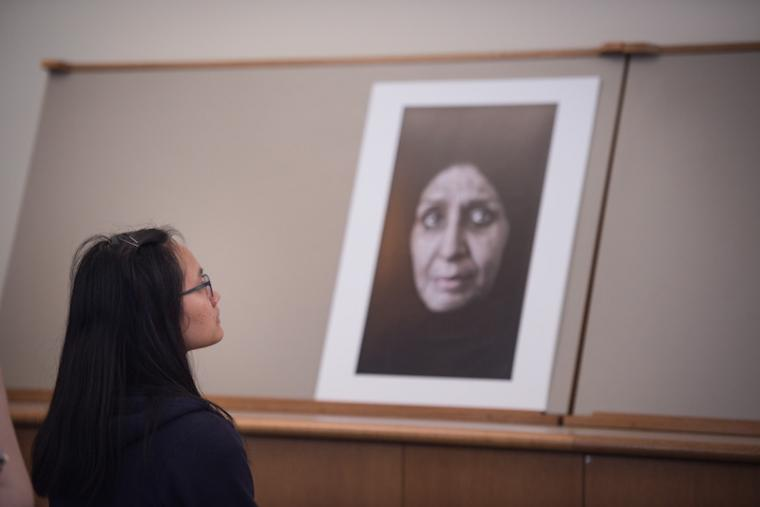 A student studies a large photo of the face of an older woman