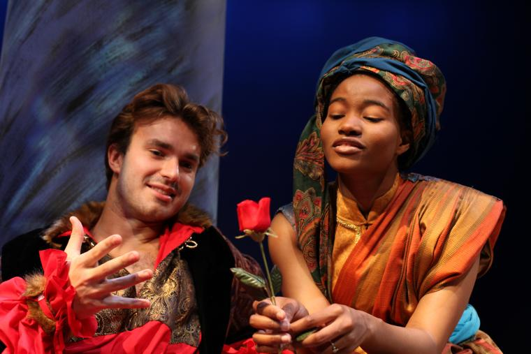 An actor hands a rose to another