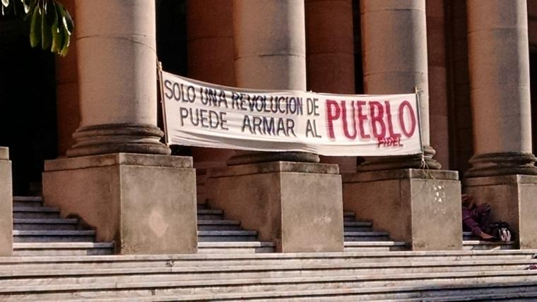 A sign hangs outside of a building at the University of Havana