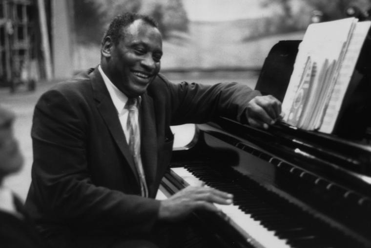 Paul Robeson seated at a piano, sharing a laugh with someone. Black and white photo.