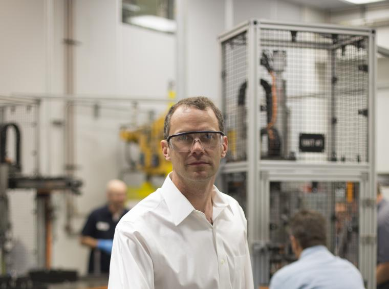 A man in a large workshop wears safety goggles and a white dress shirt. Behind him are two workers and a metal cage containing an apparatus.