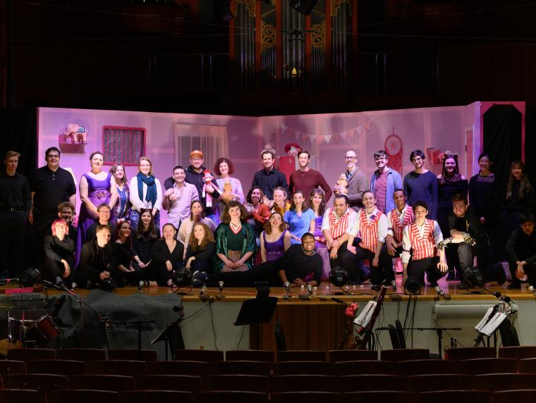 participants in an opera production gather together on stage