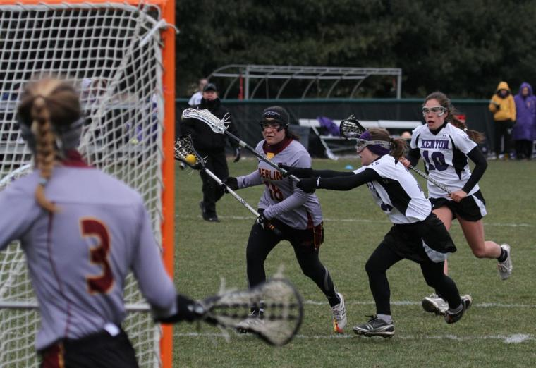 Oberlin womens lacrosse player running towards the opposing net against the Kenyon team